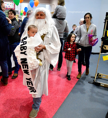 12/31/2019 MIke Orazzi | Staff Father Time Jason Fields holds Russell Waterman during the Imagine Nation's New Year's celebration on Tuesday.