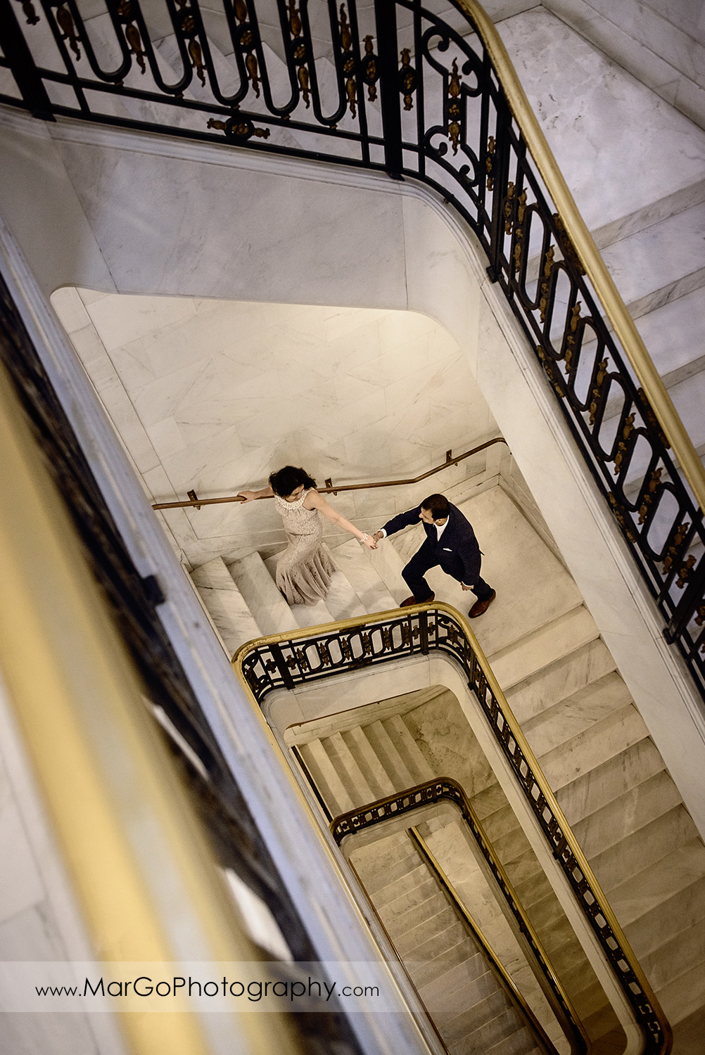 man in suit and woman in long dress walking up the stairs of San Francisco City Hall