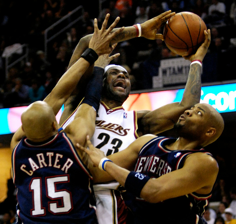. Jeff Forman/JForman@News-Herald.com LeBron James shoots over Vince Carter and Jarvis Hayes Wednesday in the fourth quarter of the Cavs win over the Nets.