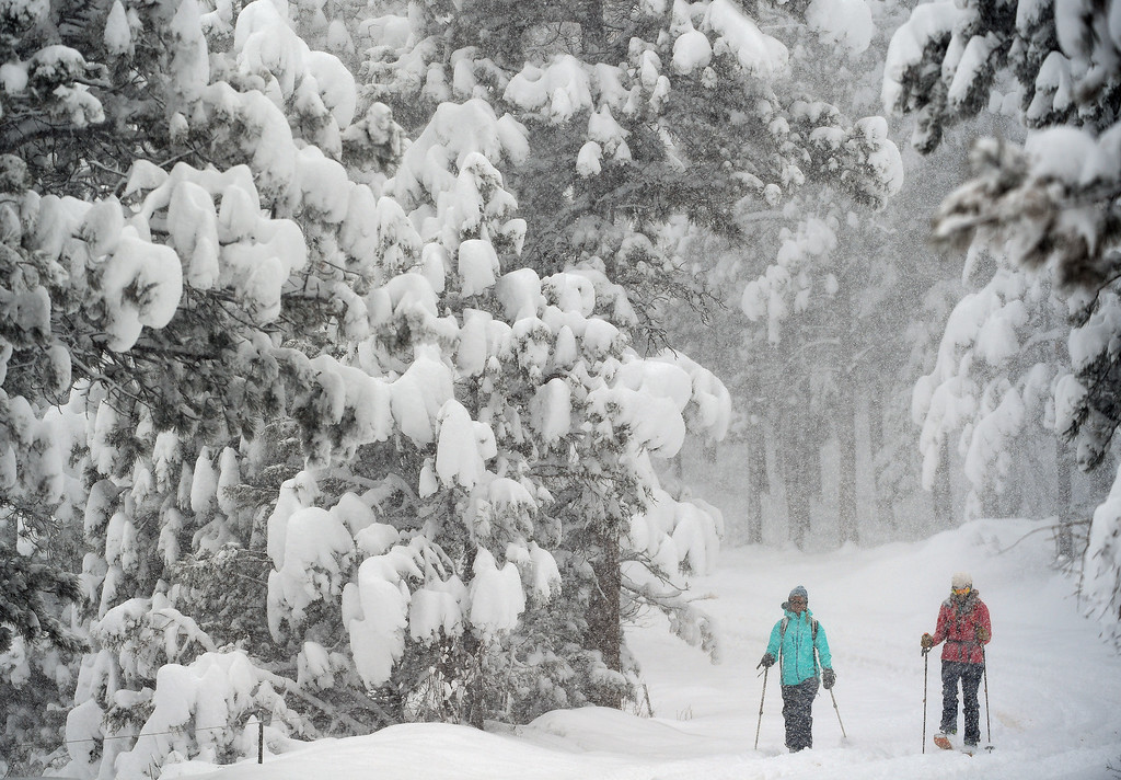 . Kestrel Hanson Neathawk, in blue on left, and Sara Born, in red, get first tracks along Ridge Road as they enjoy the almost 2 feet of snow on April 16, 2016 in Nederland, Colorado. A spring storm dumped more than 2 feet of snow in the foothills and more is expected overnight.  (Photo by Helen H. Richardson/The Denver Post)