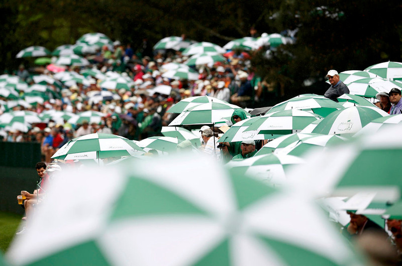 . Spectators watch from under umbrellas during final round play in the 2013 Masters golf tournament at the Augusta National Golf Club in Augusta, Georgia, April 14, 2013.  REUTERS/Mark Blinch