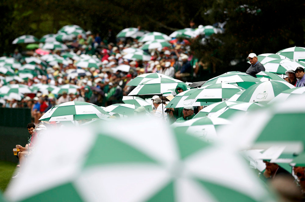 Description of . Spectators watch from under umbrellas during final round play in the 2013 Masters golf tournament at the Augusta National Golf Club in Augusta, Georgia, April 14, 2013.  REUTERS/Mark Blinch