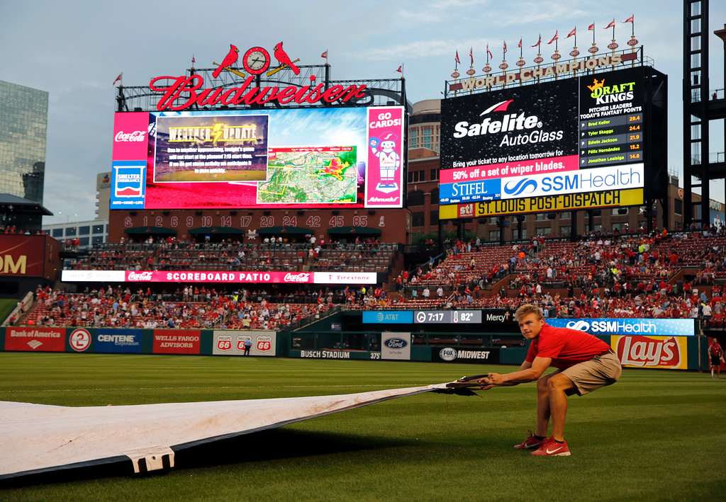 . A member of the Busch Stadium grounds crew pulls on a tarp as the field is covered in preparation for an expected rain shower before the start of a baseball game between the St. Louis Cardinals and the Cleveland Indians Monday, June 25, 2018, in St. Louis. The start of the game has been delayed. (AP Photo/Jeff Roberson)
