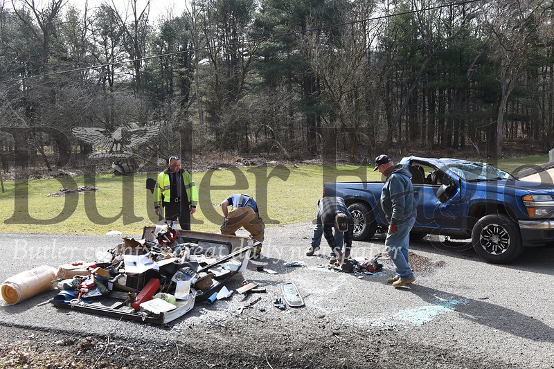 Middlesex Township Officer Conrad Pfeifer and others Monday clean up debris from a  single vehicle crash on Reamer Road.