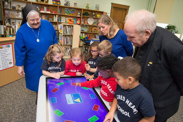 10/17/19 Wesley Bunnell | StaffrrFirst and second grade students at Sacred Heart School work with a smart table on shape recognition as Sister Mary Janice, L, School Principal Kathy Muller and Monsignor Daniel J. Plocharczyk, Pastor of Sacred Heart Church look on.