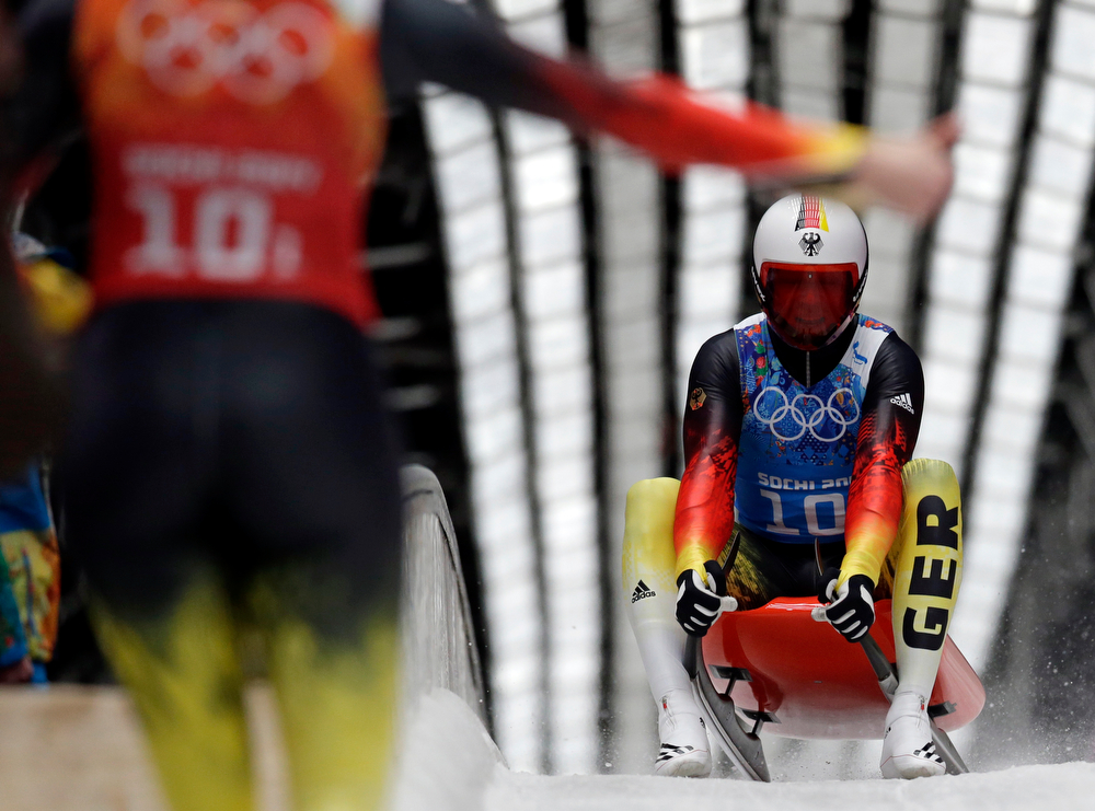 . Germany\'s Felix Loch is greeted in the finish area by teammate Natalie Geisenberger during the luge team relay competition at the 2014 Winter Olympics, Thursday, Feb. 13, 2014, in Krasnaya Polyana, Russia. The German team won the gold medal. (AP Photo/Michael Sohn)
