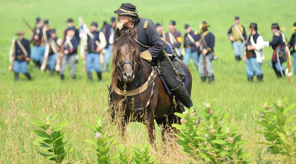 ". A Union solider dodges ""bullets\"" while on horseback during the Blue-Grey Alliance event at the Bushey Farm on June 28, 2013. LEBANON DAILY NEWS - JEREMY LONG"
