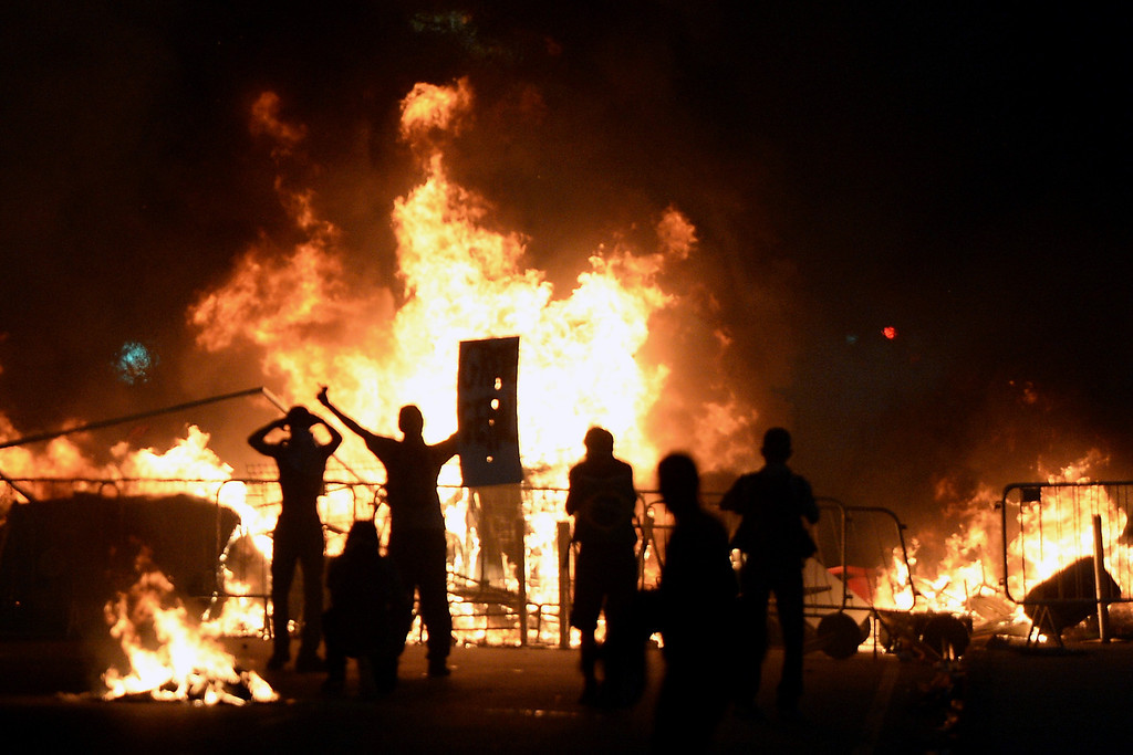 . Demonstrators stand next to a fire during a protest part of what is now called the \'Tropical Spring\' against corruption and price hikes, on June 20, 2013, in Rio de Janeiro.  AFP PHOTO / LLUIS  GENE/AFP/Getty Images