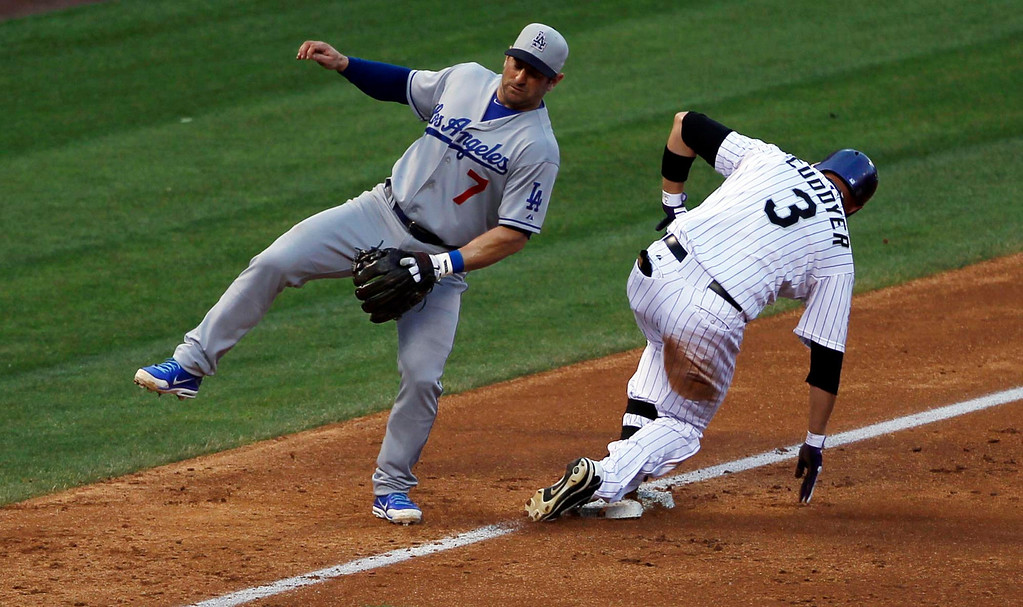 . Los Angeles Dodgers third baseman Nick Punto, left, tries to stay on his feet as Colorado Rockies\' Michael Cuddyer advances to third base on a throwing error by Dodgers shortstop Hanley Ramirez in the third inning of a baseball game in Denver, Thursday, July 4, 2013. Cuddyer had doubled-in two runners to start the play. (AP Photo/David Zalubowski)