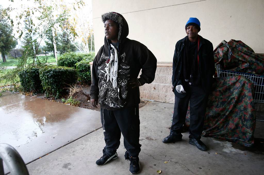 . Homeless sisters Lavella Perry, 29, left, and Keisha Perry, 24 wait out the storm under an overhang at the Tully Community Branch library in San Jose, Calif., on Thursday, Dec. 11, 2014. Both have been homeless since July. (Gary Reyes/Bay Area News Group)