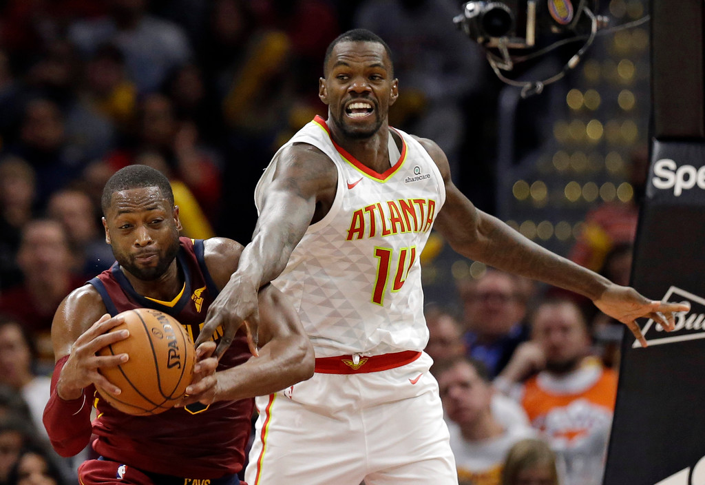 . Cleveland Cavaliers\' Dwyane Wade (9) and Atlanta Hawks\' Dewayne Dedmon (14) battle for a rebound in the second half of an NBA basketball game, Sunday, Nov. 5, 2017, in Cleveland. (AP Photo/Tony Dejak)
