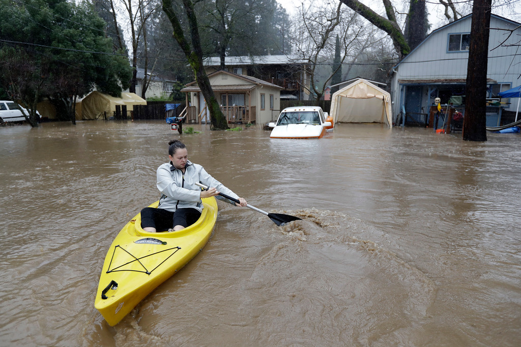 . Rachel Turner uses a kayak to access her flooded home Tuesday, Feb. 7, 2017, in Felton, Calif. Flash flood watches are in place for parts of Northern California down through the Central Coast as heavy rains swamp roads and threaten to overtop rivers and creeks. (AP Photo/Marcio Jose Sanchez)