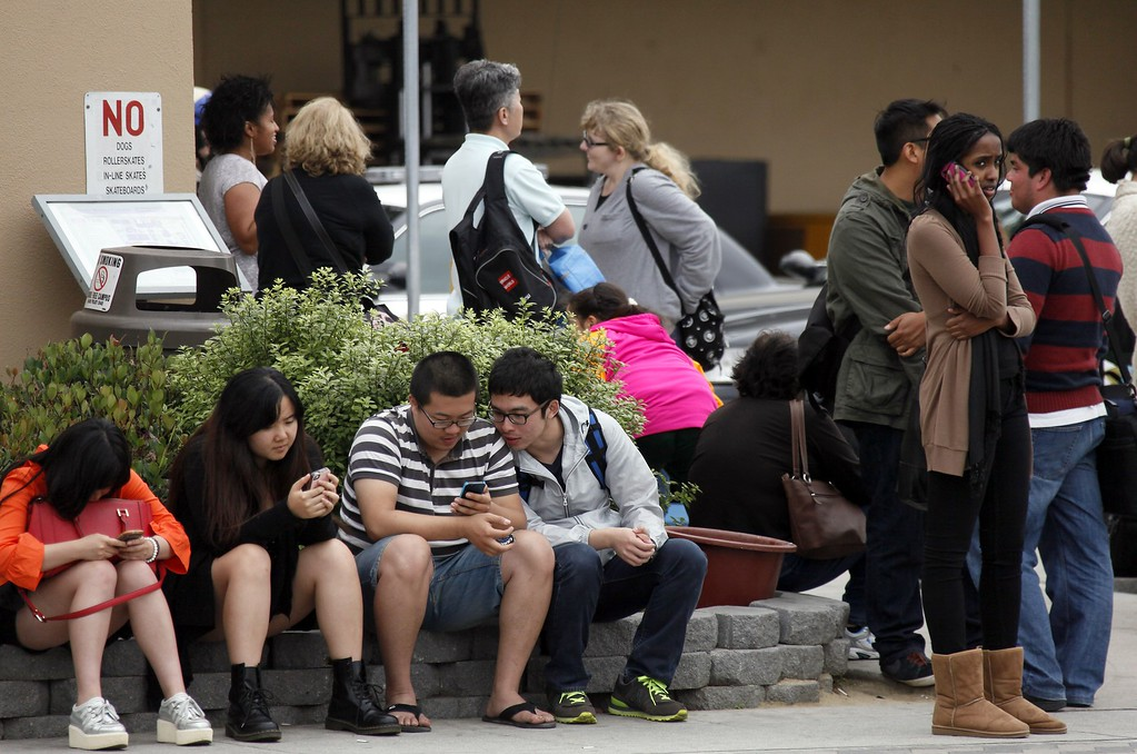 . Santa Monica College students wait for police clearance to pick up their vehicles after a shooting on campus Friday June 7, 2013 in Santa Monica. A gunman with an assault-style rifle killed at least six people in Santa Monica on Friday before police shot him to death in a gunfight in the Santa Monica College library. (AP Photo/Nick Ut)
