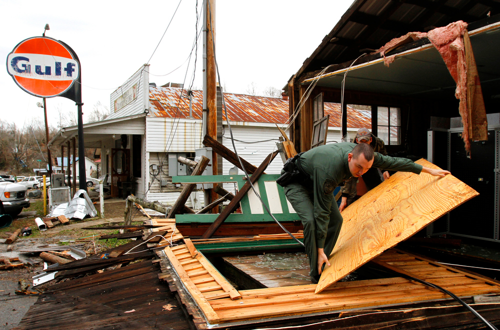 . Hickman County Sheriff, Cody Woods helps remove debris from a house after a storm ripped through early morning on Wednesday, Jan. 30, 2013, in Coble, Tenn.   A line of strong storms is pushing eastward across Tennessee, triggering tornado warnings and producing strong downpours of rain. (AP Photo/Butch Dill)