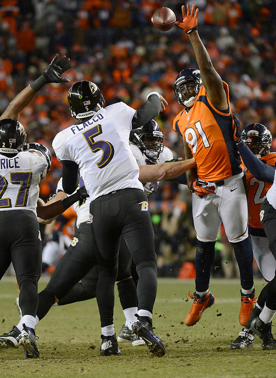 . Denver Broncos defensive end Robert Ayers (91) reaches for a pass thrown by Baltimore Ravens quarterback Joe Flacco (5). The Denver Broncos vs Baltimore Ravens AFC Divisional playoff game at Sports Authority Field Saturday January 12, 2013. (Photo by Joe Amon,/The Denver Post)