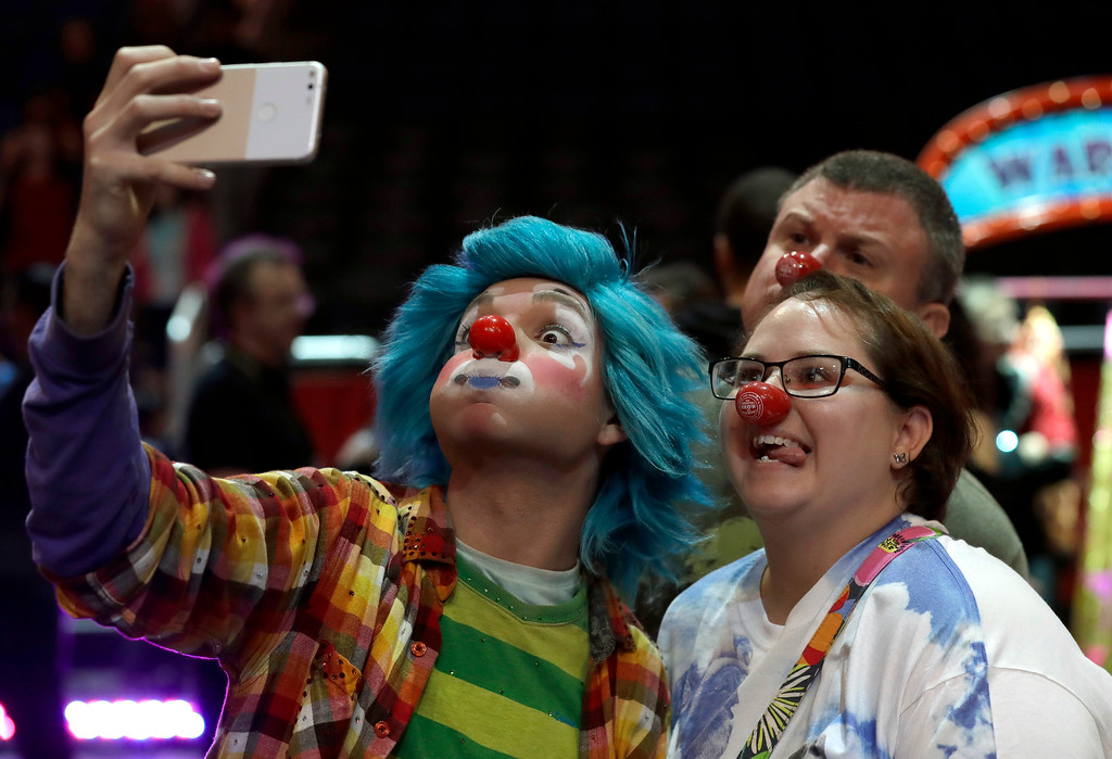 ". A Ringling Bros. and Barnum & Bailey clown takes a selfie with Jennifer and Kevin Fox, of Fort Pierce, Fla., during a pre show for fans Saturday, Jan. 14, 2017, in Orlando, Fla. The Ringling Bros. and Barnum & Bailey Circus will end the ""The Greatest Show on Earth\"" in May, following a 146-year run of performances. Kenneth Feld, the chairman and CEO of Feld Entertainment, which owns the circus, told The Associated Press, declining attendance combined with high operating costs are among the reasons for closing. (AP Photo/Chris O\'Meara)"
