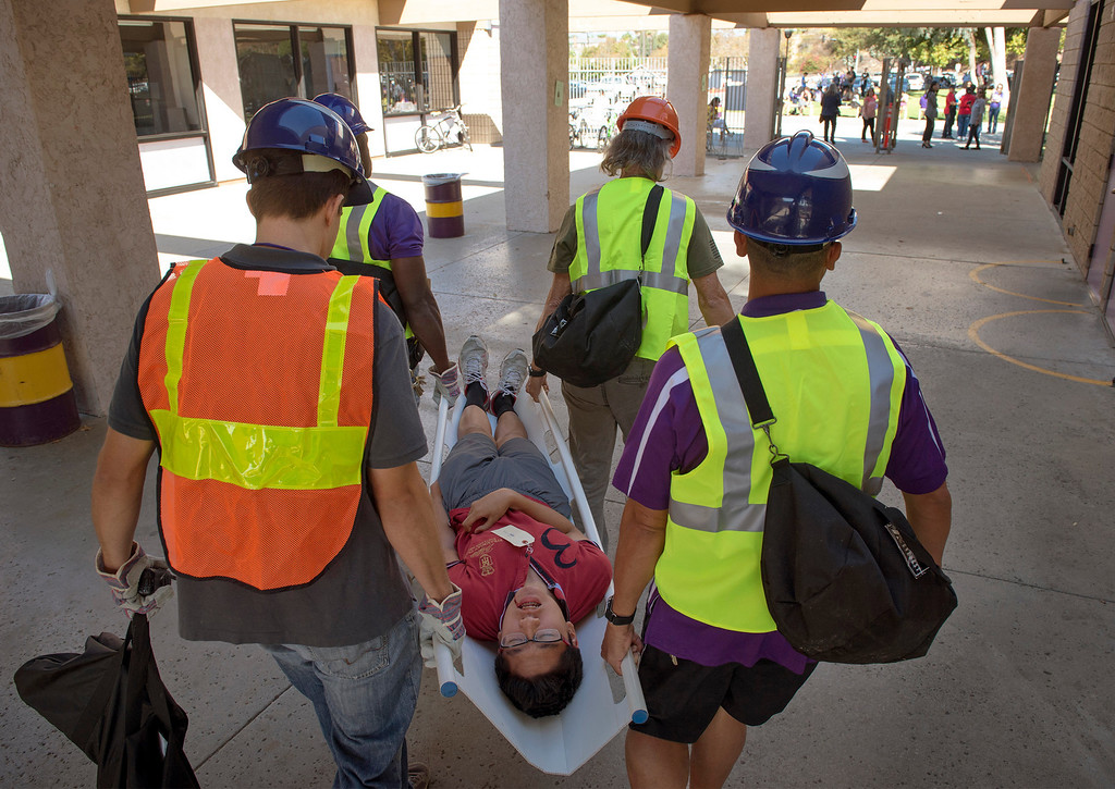 ". Diamond Bar High staff members carry an ""injured\"" student to triage during the Great ShakeOut earthquake drill at the Diamond Bar campus October 17, 2013.  (Staff photo by Leo Jarzomb/SGV Tribune)"