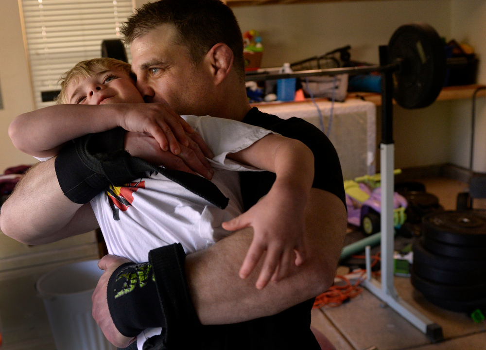 . Dave Nowick does his daily Olympic-style weight-lifting workout in his garage at his Aurora home. His sons and his daughter often join him in the workout. Today, five-year-old Oz joins him and after finishing his workout, he scoops Oz up for a wrestler\'s hug. (Photo by Kathryn Scott Osler/The Denver Post)