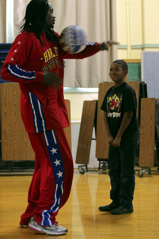 . Harlem Globetrotters� Slick Willie Shaw shows Laurel Elementary School student Kimani Rayfield, 9, one of the team\'s trademark basketball skills that he wants Rayfield to try and copy during a visit in Oakland, Calif., on Wednesday, Jan. 16, 2013. (Anda Chu/Staff)