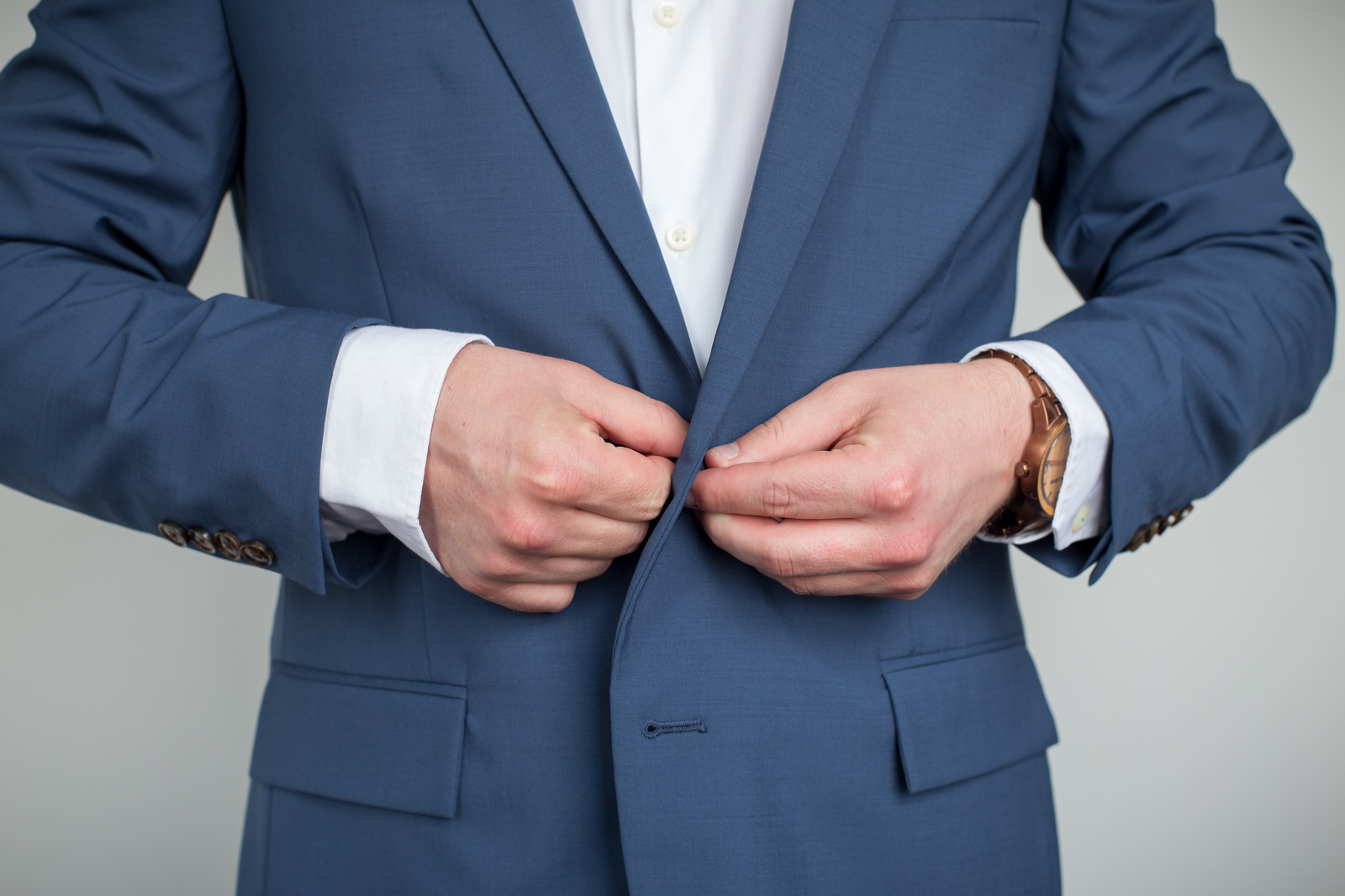 a man buttoning a blue suit wearing a copper and wood wrist watch