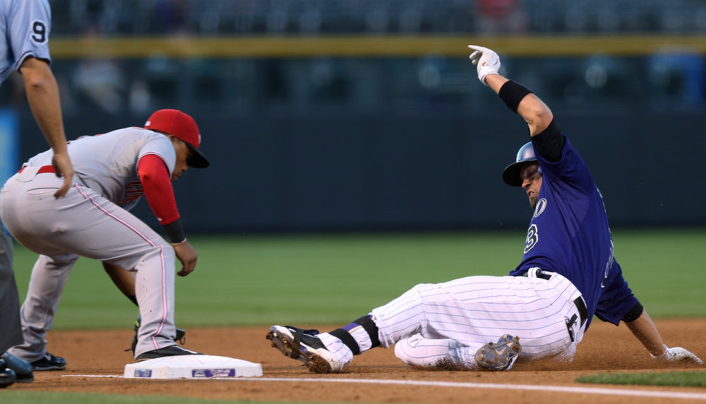 . Cincinnati Reds third baseman Ramon Santiago, left, fields throw as Colorado Rockies\' Michael Cuddyer slides safely into third base with a triple in the first inning of a baseball game in Denver on Sunday, Aug. 17, 2014. The game is being made up after it was postponed on Saturday by a water main break that left the stadium waterless. (AP Photo/David Zalubowski)