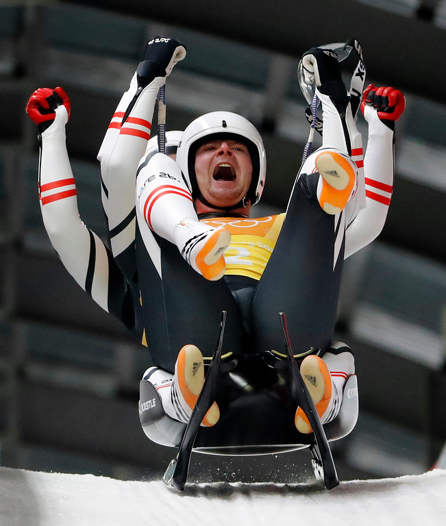 . Peter Penz and Georg Fischler of Austria react in the finish area after winning the bronze medal in the luge team relay at the 2018 Winter Olympics in Pyeongchang, South Korea, Thursday, Feb. 15, 2018. (AP Photo/Andy Wong)