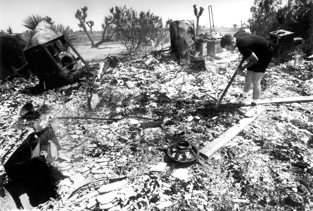 . June 28, 1992: Dennis Morrison searches for his keys in the ashes of a fire-gutted trailer in Flamingo, CA.  Daily News file photo
