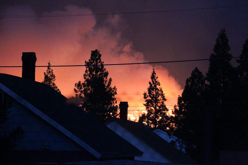 . The Boles fire burns along a ridge Monday, Sept. 15, 2014, in Weed, Calif. The, fire driven by fierce winds, raced through a small town near the Oregon border on Monday, burning a church to the ground, damaging or destroying 100 homes and prompting evacuation orders for at least 1,500 people, authorities said.(AP Photo/The Record Searchlight, Greg Barnette)