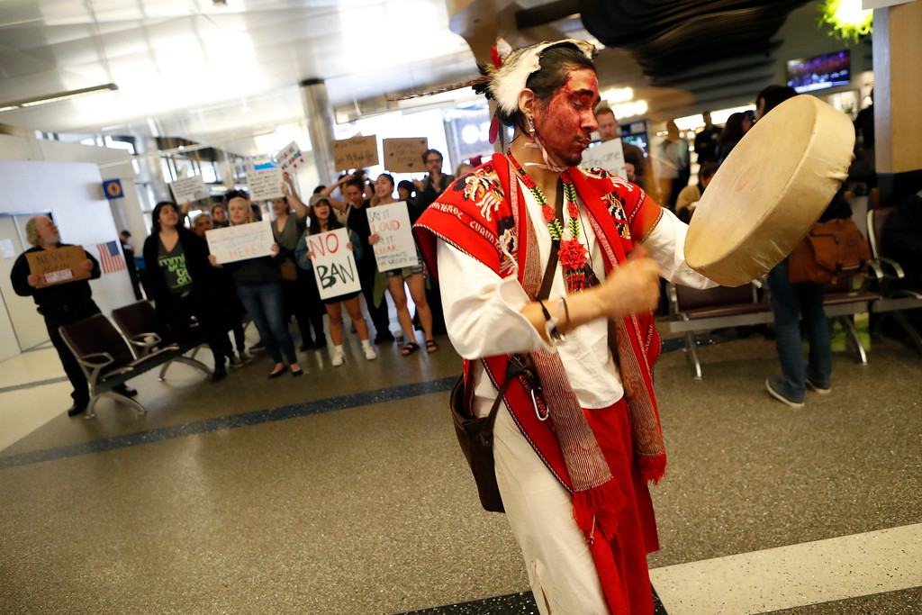 . Chichiltic Meztli plays the drum in front of demonstrators as protests against President Donald Trump\'s executive order banning travel from seven Muslim-majority countries continue at Los Angeles International Airport Sunday, Jan. 29, 2017. (AP Photo/Ryan Kang)