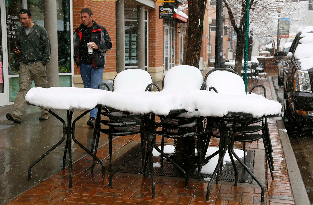 . Men walk past snow-covered cafe tables in downtown Golden, Colorado May 1, 2013.       REUTERS/Rick Wilking