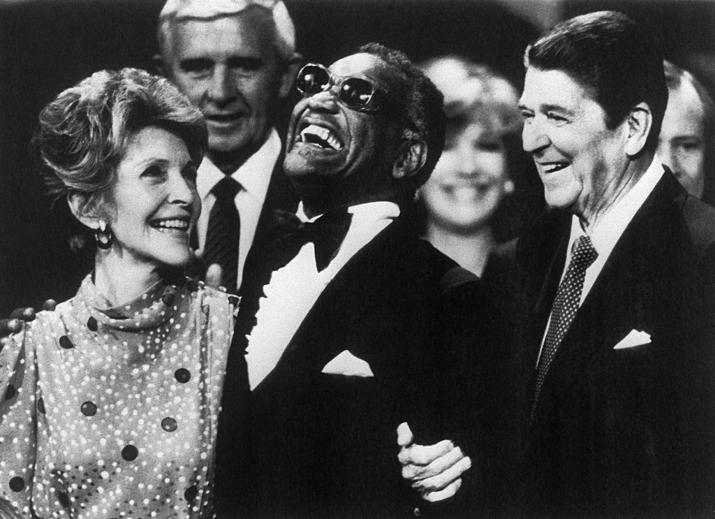 """. US music legend Ray Charles (C) joins US President Ronald Reagan and First Lady Nancy Reagan on the podium after singing \""""America The Beautiful\"""" to GOP delegates in Dallas in August, 1984. (DON RYPKA/AFP/Getty Images)"""