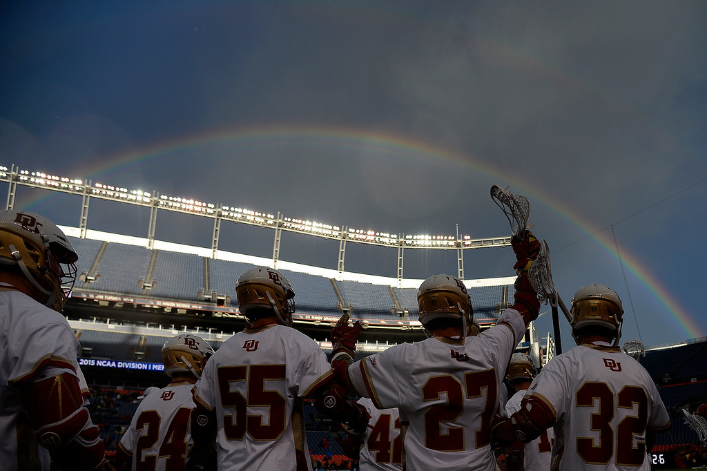 . Denver Pioneers players celebrate the final seconds of the match against the Ohio State Buckeyes as a rainbow takes the sky during the second half of Denver\'s 15-13 NCAA tournament quarterfinal win. The Denver Pioneers played the Ohio State Buckeyes at Sports Authority field at Mile High on Saturday, May 16, 2015. (Photo by AAron Ontiveroz/The Denver Post)