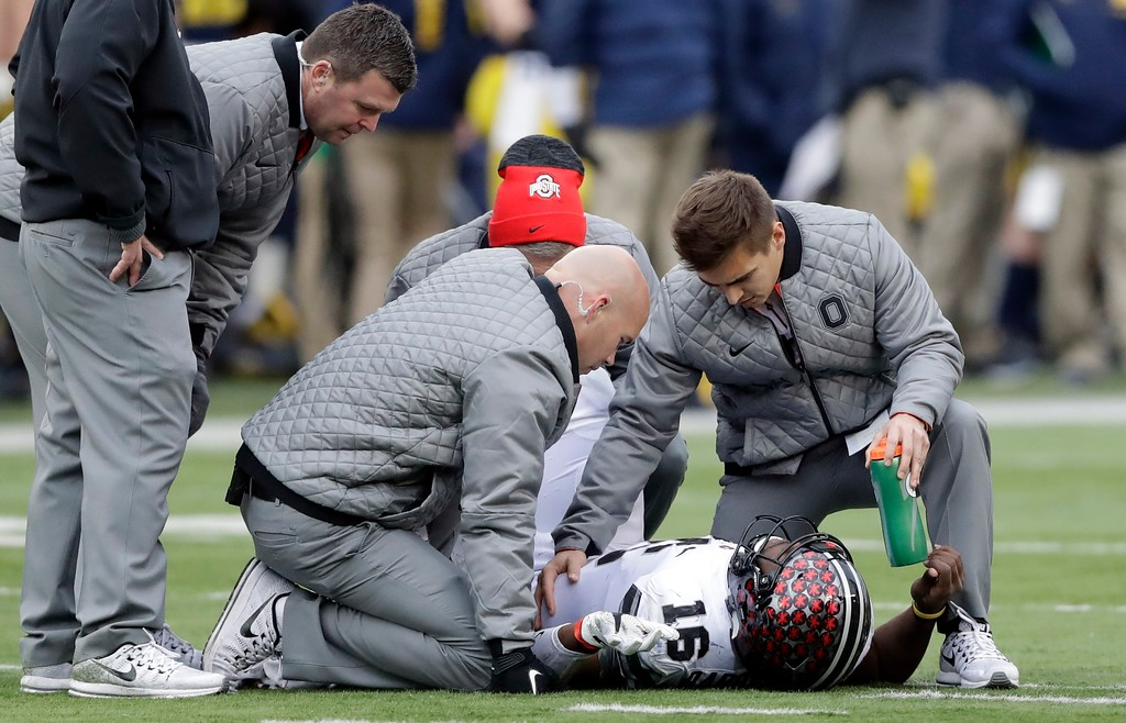 . Ohio State quarterback J.T. Barrett (16) is looked at by team officials after being sacked during the second half of an NCAA college football game, Saturday, Nov. 25, 2017, in Ann Arbor, Mich. Barrett did not return after the sack. (AP Photo/Carlos Osorio)