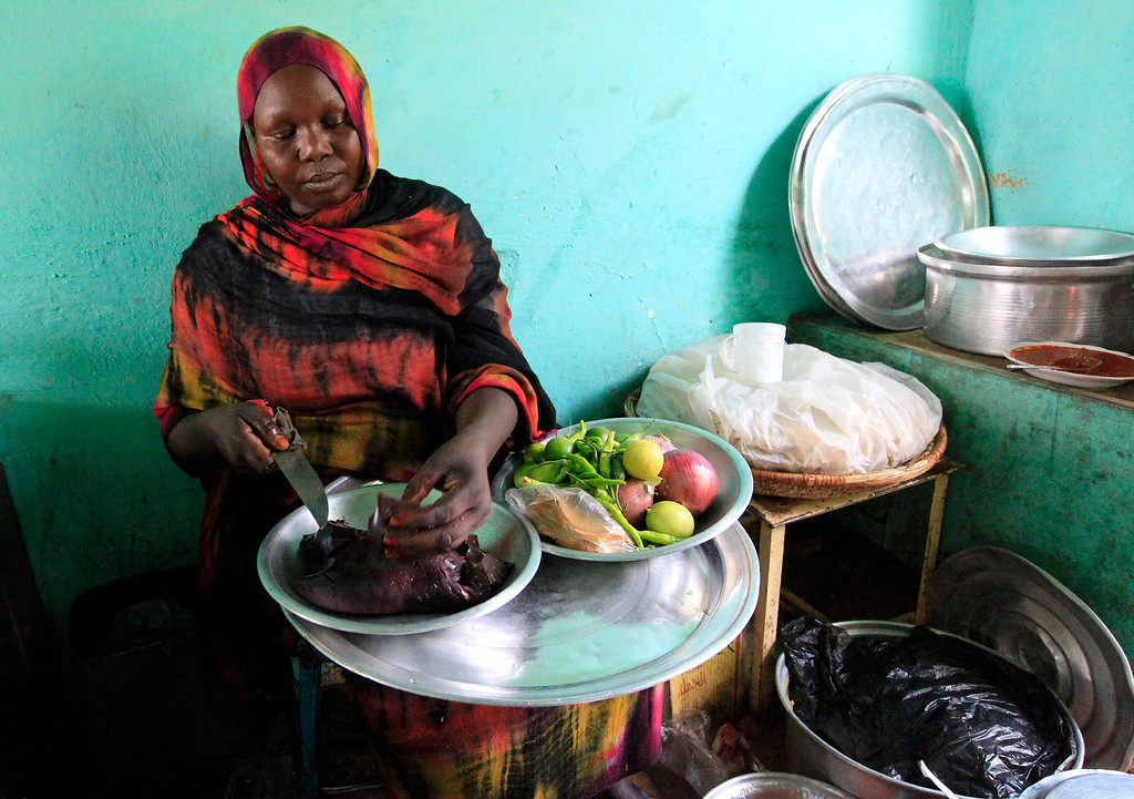 . A woman prepares a dish of camel liver at her shop in Tamboal village market in Al Jazeera April 16, 2011. According to the Sudanese Ministry of Animals Resources in 2003, the country produced about 72,000 to 81,000 tonnes of camel meat annually from 1996 to 2002.    REUTERS/Mohamed Nureldin Abdallah
