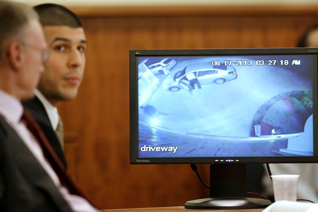 . Former New England Patriots football player Aaron Hernandez and defense attorney Charles Rankin, left, look on as video from Hernandez\'s home is displayed on a monitor during his murder trial, Thursday, Jan. 29, 2015, in Fall River, Mass. Hernandez is charged with killing semiprofessional football player Odin Lloyd, 27, in June 2013.  (AP Photo/Steven Senne, Pool)