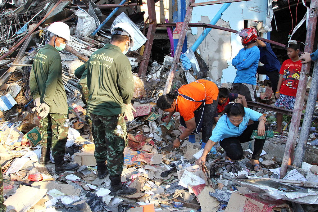 . Residents, right, sift through the wreckage of a scrap shop as Thai soldiers, left, watch after a bomb explosion in Bangkok, Thailand Wednesday, April 2, 2014.  (AP Photo/Apichart Weerawong)