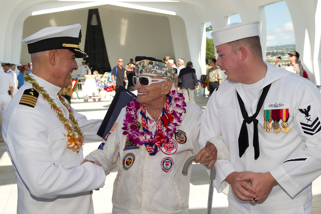 . Navy chaplain Sal Aguliera, left, shares a moment with Pearl Harbor survivor Allen Bodenlos, center, who is being escorted by Navy petty officer Michael Temple aboard the USS Arizona Memorial during the ceremony commemorating the 72nd anniversary of the attack on Pearl Harbor, Saturday, Dec. 7, 2013, in Honolulu.  (AP Photo/Marco Garcia)