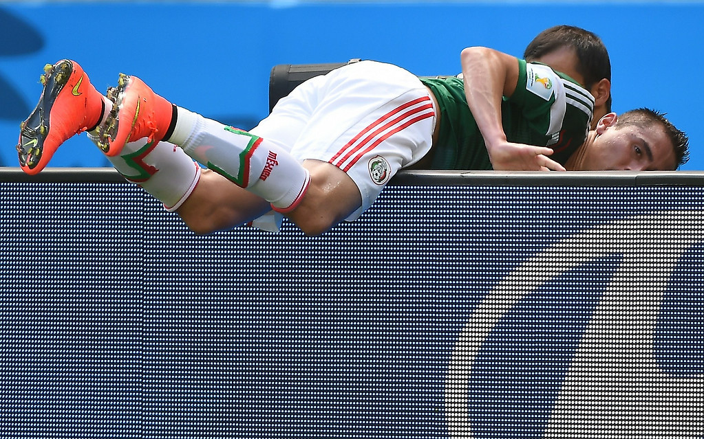 . Mexico\'s defender Paul Aguilar falls over an advertising barrier during a Round of 16 football match between Netherlands and Mexico at Castelao Stadium in Fortaleza during the 2014 FIFA World Cup on June 29, 2014.  EMMANUEL DUNAND/AFP/Getty Images