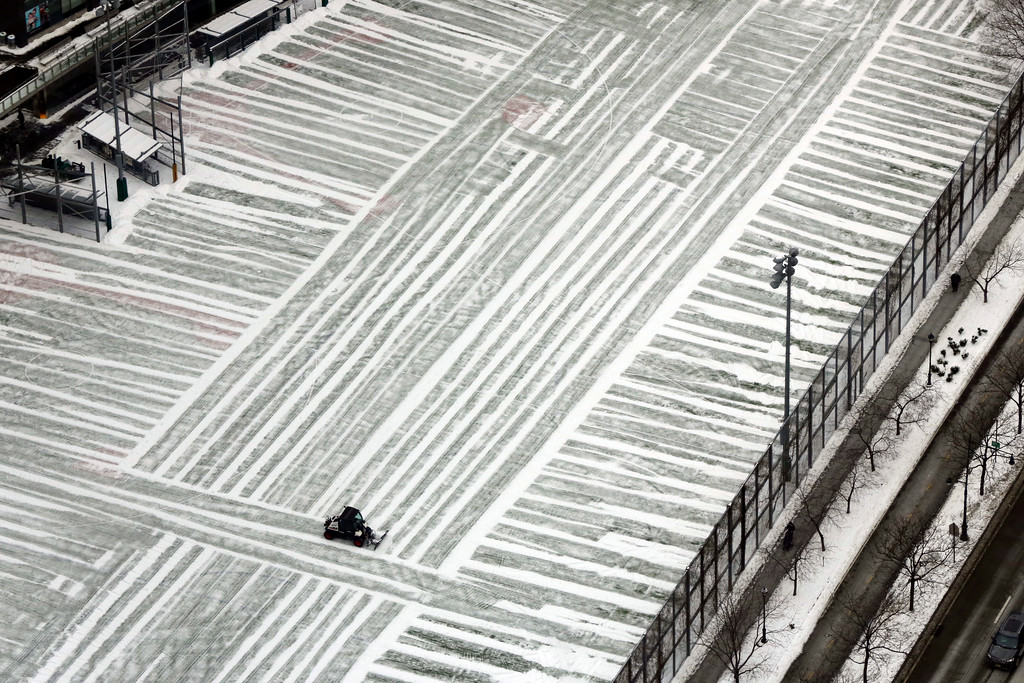 . A lone plow clears a playground in lower Manhattan, photographed from New York\'s One World Trade Center building, Monday, Jan. 9, 2017. As the East Coast waits to thaw out from a weekend icy mess, another storm is bringing rain and the potential of the worst flooding in more than a decade to the West coast. (AP Photo/Richard Drew)
