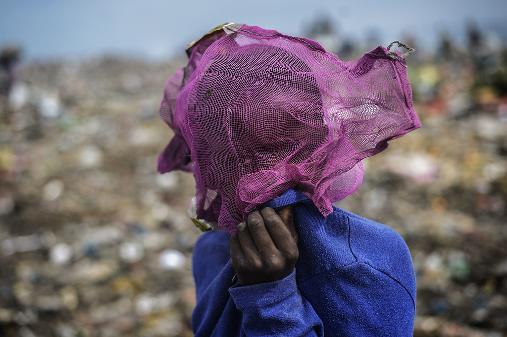 . A Mozambican boy covers his face as others sift through garbage at the Maputo municipal garbage dumping site in Maputo on October 14, 2014. GUERCIAGIANLUIGI GUERCIA/AFP/Getty Images