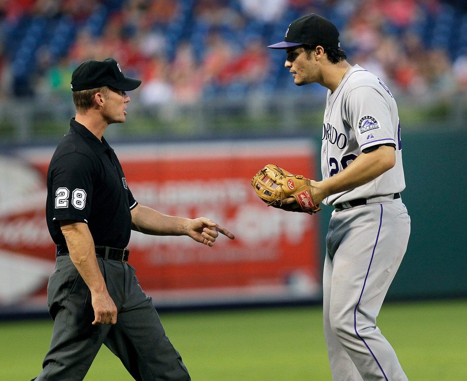 . Colorado Rockies third baseman Nolan Arenado questions the call with third base umpire Jim Wolf (28) after the Philadelphia Phillies\' Domonic Brown was called safe in the second inning of a baseball game, Thursday, Aug. 22, 2013, in Philadelphia. (AP Photo/Laurence Kesterson)