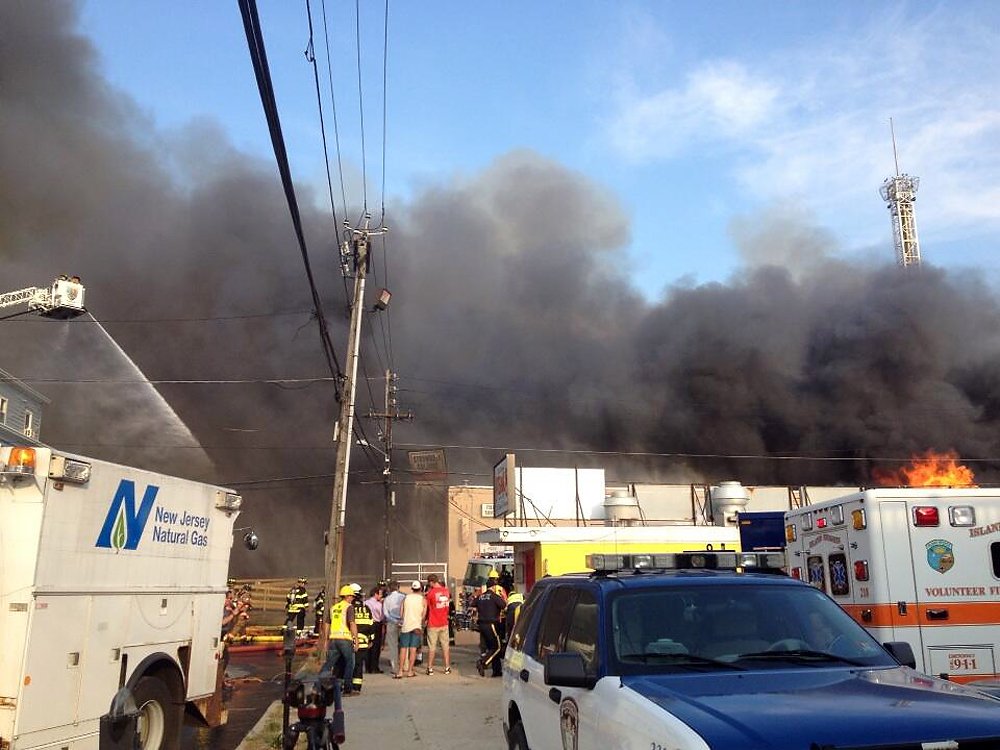 Description of . Billowing black smoke rises as firefighters battle a raging fire on the boardwalk in Seaside Heights, N.J. that apparently started in an ice cream shop and has spread several blocks down, Thursday, Sept. 12, 2013. The boardwalk was damaged in Superstorm Sandy and was being repaired. (AP Photo/The Asbury Park Press, Erik Larsen)