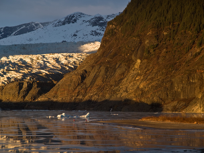 A typical winter scene in Juneau, the cliffs next to the Mendenhall Glacier, in unusually good light, the lake frozen,  two people out for a walk. The winter of 2010 has been unusually warm thanks to the El Nino weather pattern.