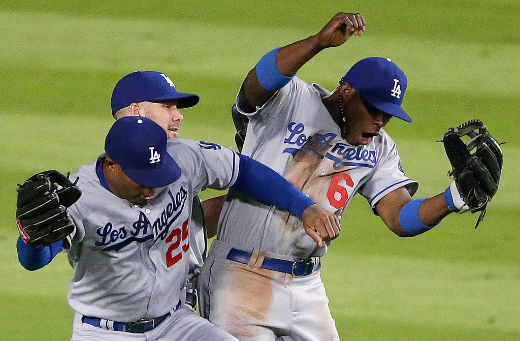 . Los Angeles Dodgers left fielder Carl Crawford (25) Los Angeles Dodgers third baseman Jerry Hairston Jr. (6) and Los Angeles Dodgers second baseman Skip Schumaker (55) celebrate after Game 1 of the National League Divisional Series against the Atlanta Braves, Friday, Oct. 4, 2013, in Atlanta. The Dodgers won 6-1. (AP Photo/David Goldman)