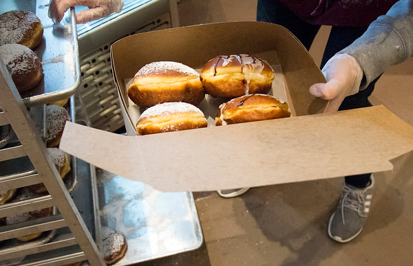 02/20/20 Wesley Bunnell | StaffrrAnna Czerkiewicz puts together a box of paczki for a customer as customers wait patiently in line at Roly Poly Bakery on Thursday February 20, 2020.