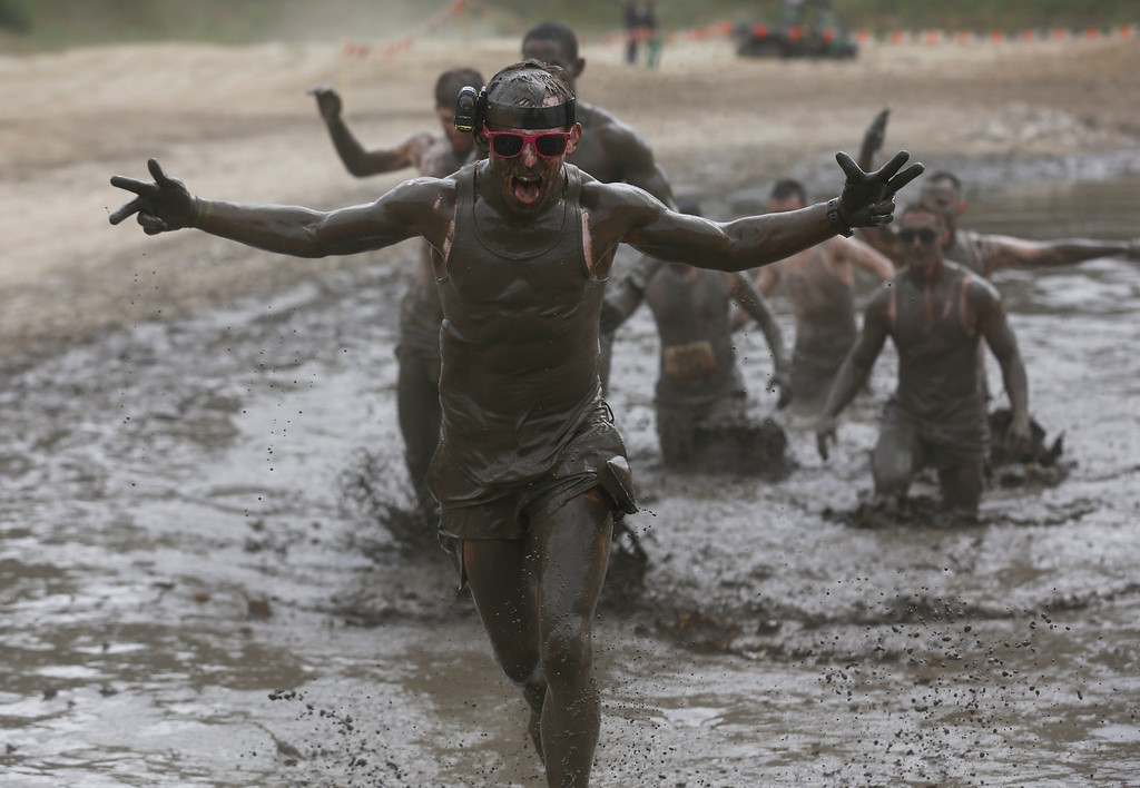 ". A participant of the ""Tough Mudder\"" endurance event series runs through the \""mud-mile obstacle\"" in the Fursten Forest, a former British Army training ground near the north-western German city of Osnabrueck July 13, 2013. The hardcore but un-timed event over 16 km (10 miles) was designed by British Special Forces to test mental as well as physical strength. Some 4,000 competitors had to overcome obstacles of common human fears, such as fire, water, and heights.   REUTERS/Wolfgang Rattay"