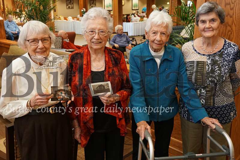 Agnes Peebles of Cranberry Township, Evelyn Smith of New Wilmington, Jane Book of New Castle and Helen Hammerschmidt of Plain Grove show off photos from the past. The women, who began meeting as women's Sunday school group in 1949, met for the 70th year Tuesday.