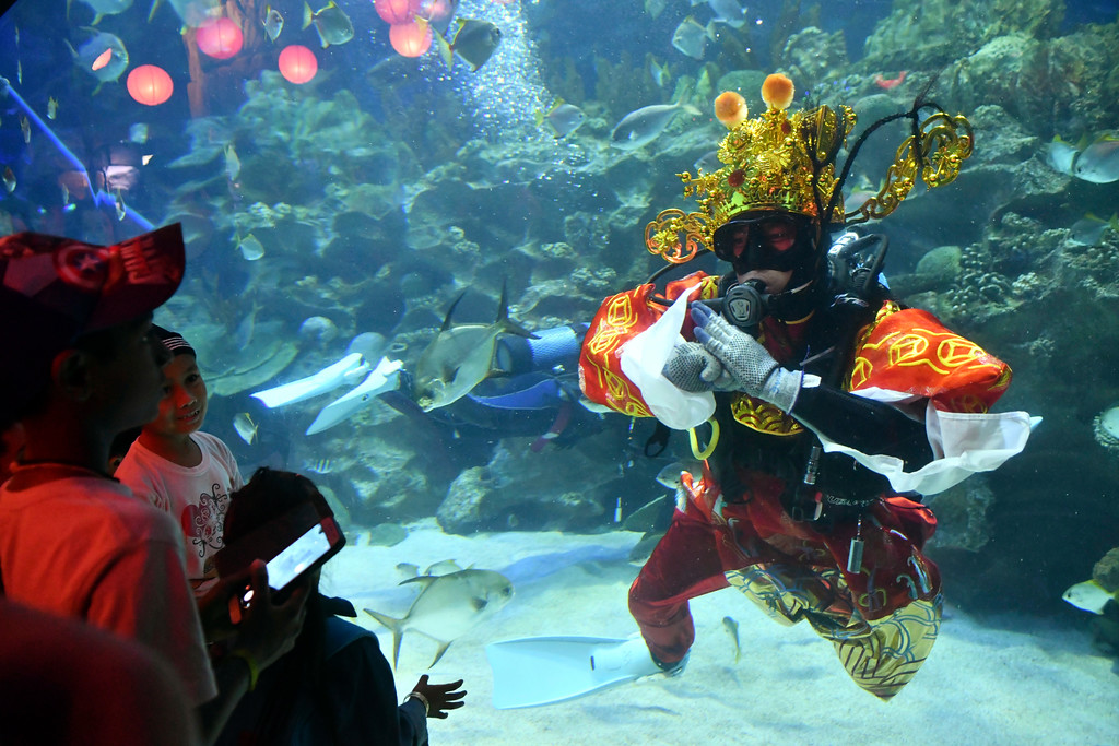 . A diver dressed in Fortune God costume greets to visitors after he fed fish as part of Chinese Lunar New Year celebrations at Aquaria KLCC underwater park in Kuala Lumpur, Malaysia, Friday, Feb. 16, 2018. The Lunar New Year which falls on Feb. 16 this year marks the Year of the Dog in the Chinese calendar. (AP Photo/Adrian Hoe)