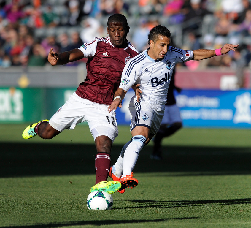 . COMMERCE CITY, CO. - OCTOBER 19: Colorado midfielder Hendry Thomas (12) pushed Vancouver forward Camilo Sanvezzo (7) off the ball in the first half. The Colorado Rapids hosted the Vancouver Whitecaps at Dick\'s Sporting Goods Park Saturday, October 19, 2013. Photo By Karl Gehring/The Denver Post