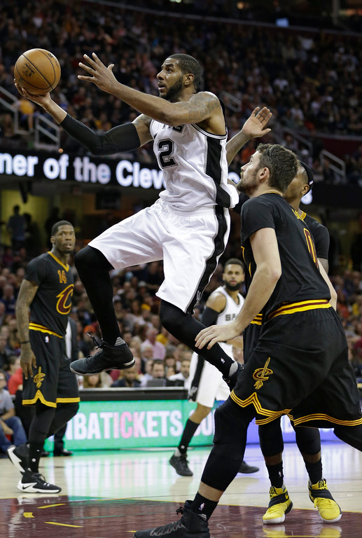 . San Antonio Spurs\' LaMarcus Aldridge, left, drives to the basket against Cleveland Cavaliers\' Kevin Love in the first half of an NBA basketball game, Saturday, Jan. 21, 2017, in Cleveland. (AP Photo/Tony Dejak)